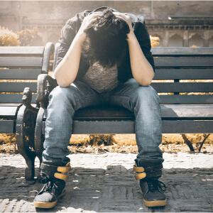 Een man zit gestrest op een bankje